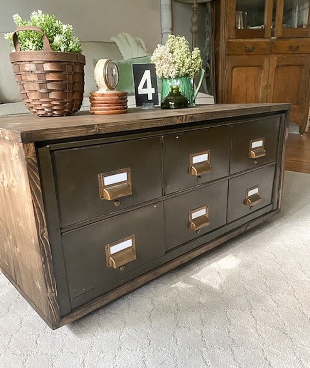 Create a DIY Industrial Coffee Table from an industrial metal drawer piece, some wood, stain and old casters to get the look you want for less!
